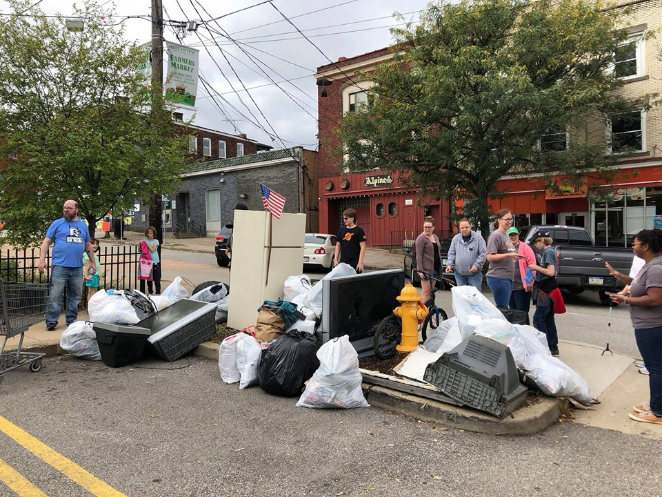 A PUB volunteer standing next to several garbage bags full of trash.